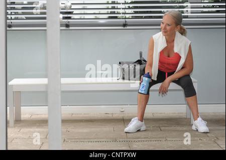Femme plus l'eau potable dans une salle de sport