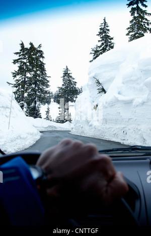 L'homme de la conduite sur route dégagé dans la neige Banque D'Images