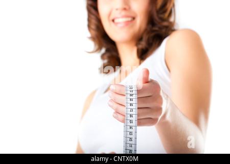 Le régime alimentaire et le poids, jeune femme avec un ruban à mesurer pour mesurer son contrôle Banque D'Images