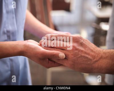 Nurse examining older mans mains Banque D'Images