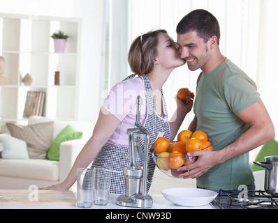 Woman kissing boyfriend dans la cuisine Banque D'Images