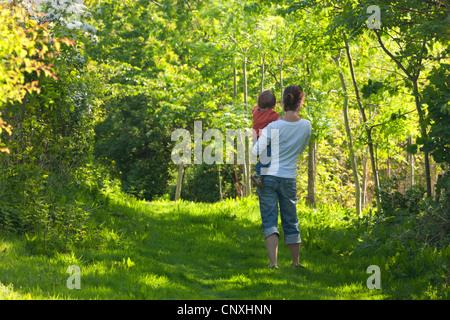Mère et fils âgé d'un an debout dans un Cutteridge caduques, bois, Devon, Angleterre. Printemps (avril) 2011. Banque D'Images