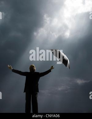 Man holding umbrella debout dans les rayons du soleil Banque D'Images