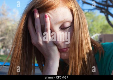 Close up de seize ans, fille de l'adolescence avec la main sur son visage. Banque D'Images