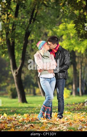 Un couple d'amoureux s'embrasser dans le parc en automne Banque D'Images