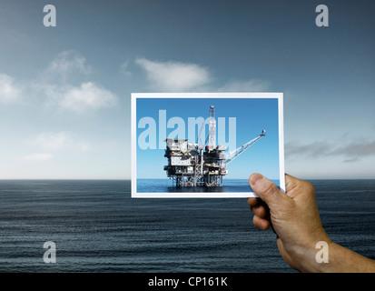 Hand Holding Photo de la plate-forme d'huile sur l'Océan Banque D'Images