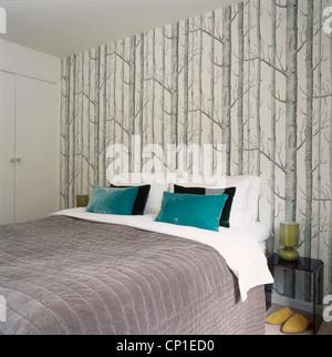 Coussins bleu sur un lit double contre mur avec du papier peint Motif arbre Banque D'Images