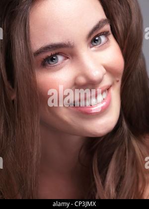 Closeup portrait of a smiling jolie jeune femme avec de beaux yeux gris