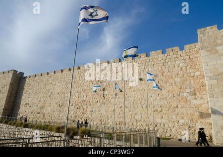 Voir des murs de la Cité avec les juifs orthodoxes et drapeau israélien. Vieille ville de Jérusalem. Israël. Banque D'Images