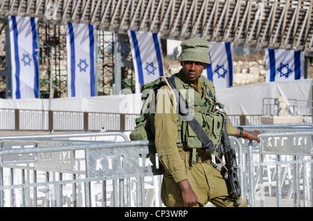 Soldat israélien au garde barrière sur Memorial Day avec des drapeaux israéliens en arrière-plan. Mur ouest. Vieille Banque D'Images