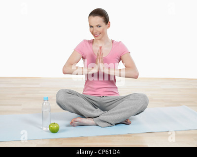 Young woman doing yoga, smiling, portrait Banque D'Images
