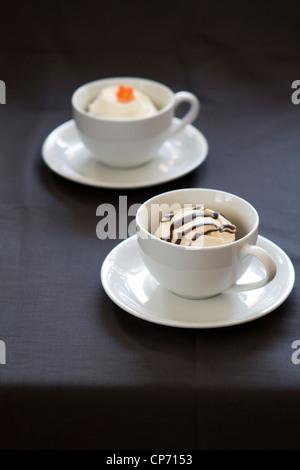Une photographie de deux tasses blanc contenant des cupcakes sur un fond sombre.