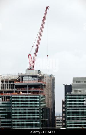 Une grue rouge sur un chantier de construction dans le quartier des affaires du centre-ville de Birmingham, England, Banque D'Images