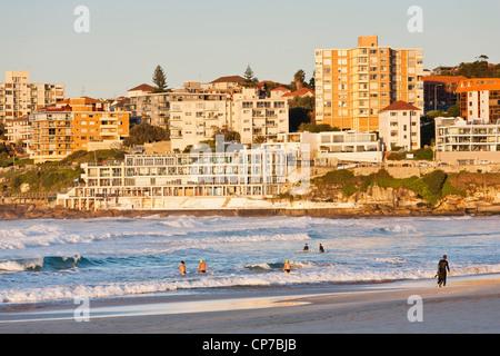 Tôt le matin, les nageurs et les surfeurs de Bondi Beach, Sydney. Les immeubles à appartements et les icebergs Club Banque D'Images