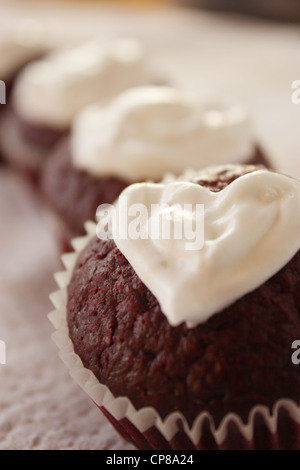 Le thème de la saint valentin red velvet cupcakes avec garniture de fromage à la crème en forme de coeur. Les cadeaux Banque D'Images