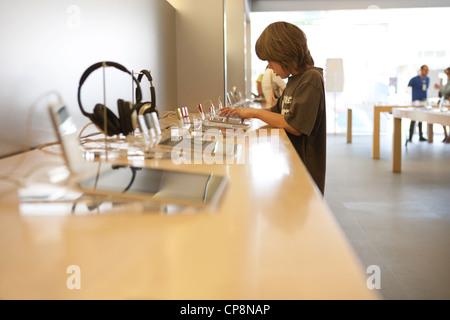 Neuf ans essaye la dernière version de tablette ipad dans un Apple store. Banque D'Images