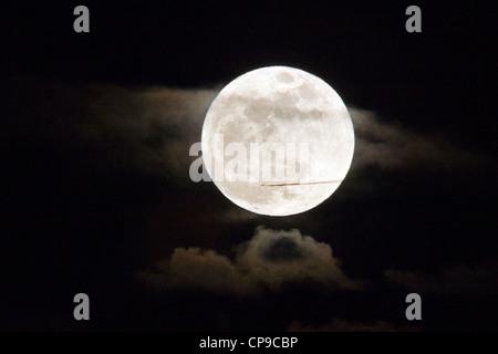 Les mouches à réaction commerciaux en face d'une pleine lune, perigree ou supermoon, qui s'élève au-dessus de Salida, Banque D'Images