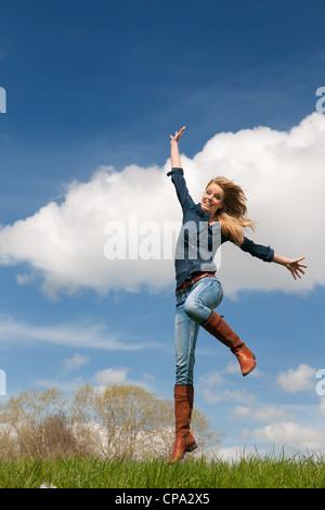 Jeune fille blonde saut avec ciel bleu et l'herbe Banque D'Images