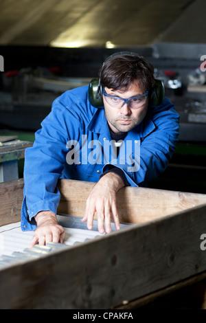 Col bleu à la machine en usine Banque D'Images