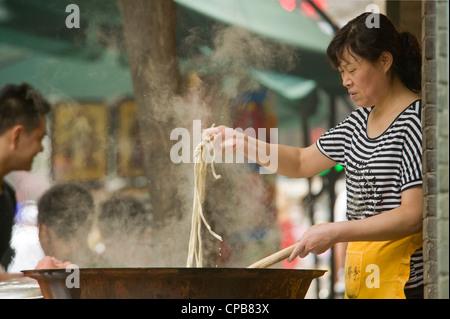 Une femme chinoise nouilles cuisine à un extérieur food de Moslem Street (Huimin Jie) à Xian. Banque D'Images