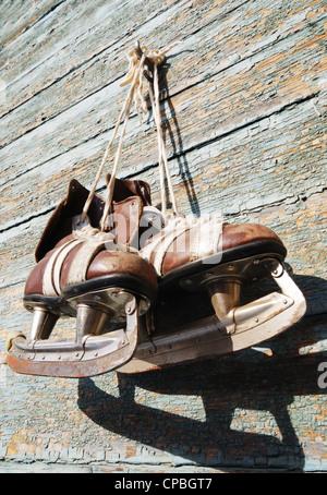 Vintage paire de patins à glace mens accrochée à un mur en bois Banque D'Images
