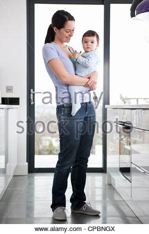 Une mère debout dans une cuisine tenant son bébé Banque D'Images