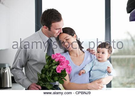 Un homme donnant à son partenaire un bouquet de roses, femme tenant leur fils bébé Banque D'Images