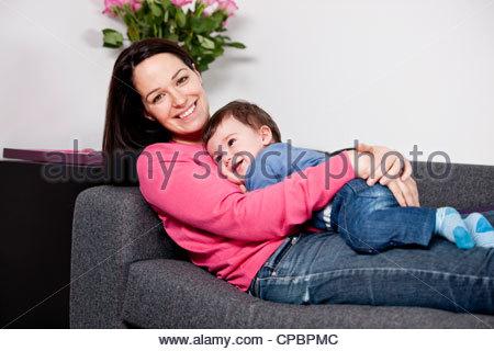 Une mère de câliner son bébé sur un canapé Banque D'Images