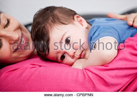 Une mère de câliner son bébé sur un canapé, Close up Banque D'Images