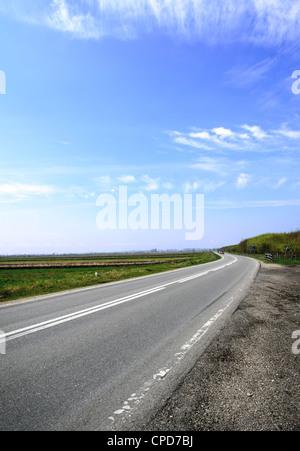 Image horizontale d'une route de campagne avec ciel bleu en été Banque D'Images
