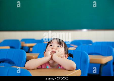Petite fille asiatique pensent encore à la salle de classe Banque D'Images