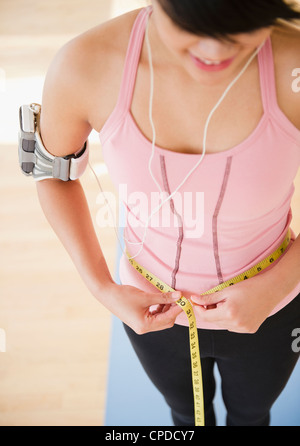 Pacific Islander woman measuring her waistline