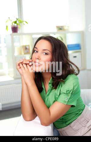 Pretty young woman sitting on sofa and looking at camera Banque D'Images