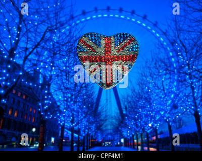 Réfléchissant en forme de coeur Union Jack Flag mousseux avec le London Eye de nuit Westminster London UK Banque D'Images