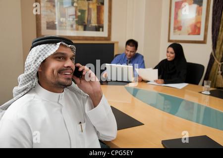Businessman using mobile phone, deux collègues en arrière-plan.