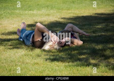 Mère et fils allongé dans l'herbe sous un arbre d'ombrage. Banque D'Images