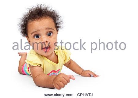Un mignon et heureux à l'âge de six mois, bébé fille de ramper sur le sol avec un fond blanc Banque D'Images