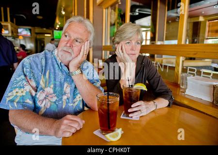 Un couple d'âge moyen semblait indifférent à l'ensemble plus de thés ensemble dans un Long Beach, CA, restaurant