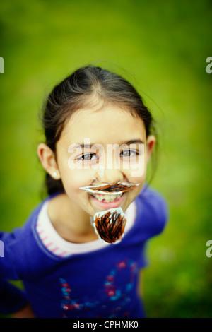 Movember. Fille avec sa barbe et moustache fait maison qu'elle a collé à son visage avec du ruban gommé. Banque D'Images