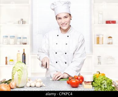 Jeune femme chef de cuisine à l'oignon coupe Banque D'Images