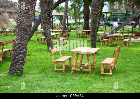 Table avec des bancs dans le jardin vert tropical sur l'herbe. Café d'été écologique. Personne ne Banque D'Images