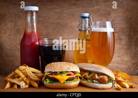 La malbouffe avec burger, hot-dog, frites, cola, du ketchup et de la bière sur un fond de bois Banque D'Images