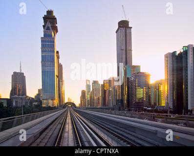 Ville moderne au coucher du soleil, passage supérieur de métro avec des rails, la ville de Dubaï en Émirats Arabes Banque D'Images