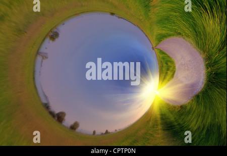 Image panoramique, ressemble à une planète verte avec le lever du soleil sur la route d'asphalte Banque D'Images