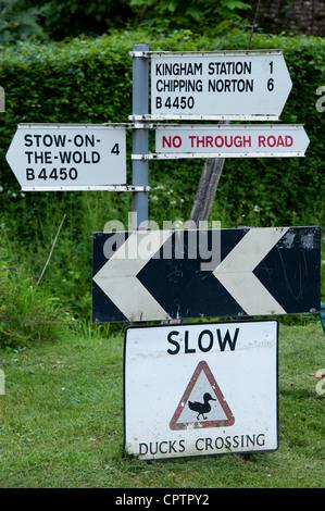 Canards lente panneau de passage à niveau à côté d'un panneau routier. Kingham, Oxfordshire, Cotswolds , Angleterre Banque D'Images