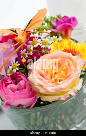 Un petit vase de fleurs sur une table à la réception de mariage.