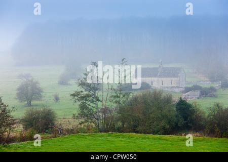 Scène Misty et st oswald's Church, une chapelle à distance dans un champ, à Widford dans la région des Cotswolds près de Burford, Oxfordshire, UK