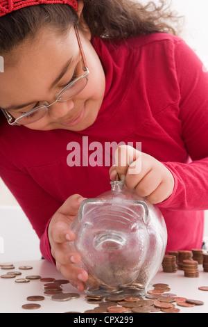 Jeune fille le passage des pièces dans piggy bank Banque D'Images