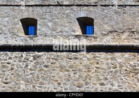 Un vieux mur de prison avec des fenêtres dans le ciel bleu sur château Forchtenstein Banque D'Images