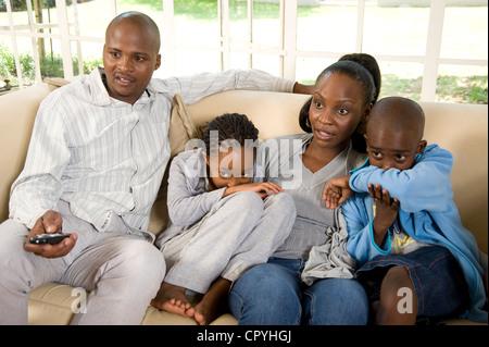 Les jeunes de la famille africaine s'asseoir ensemble sur un canapé Banque D'Images